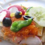 Kanapka z serem, marchewką, rzodkiewką, ogórkiem, papryką, kukurydza i oliwkami